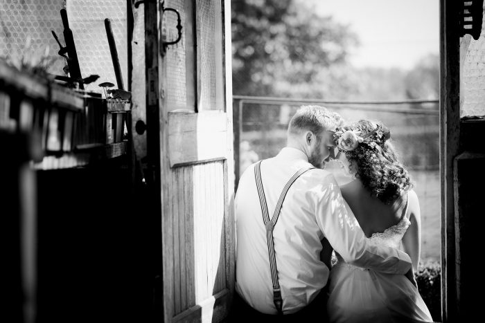black and white wedding photograph of bride and groom sitting together hugging and smiling