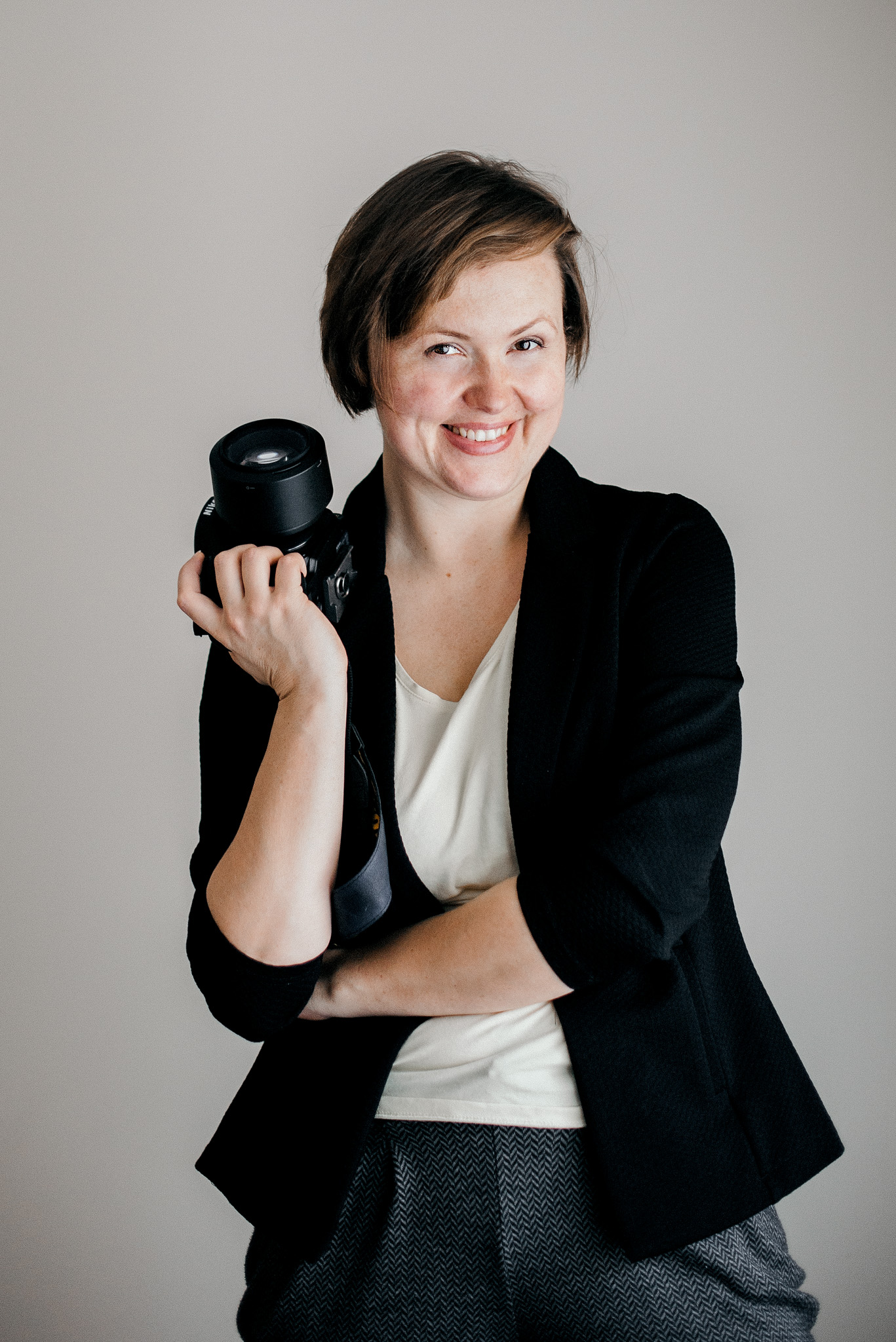 Portrait of Barbara the wedding photographer smiling and holding camera